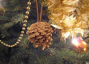 Pomme de pin et guirlande en billes dorées